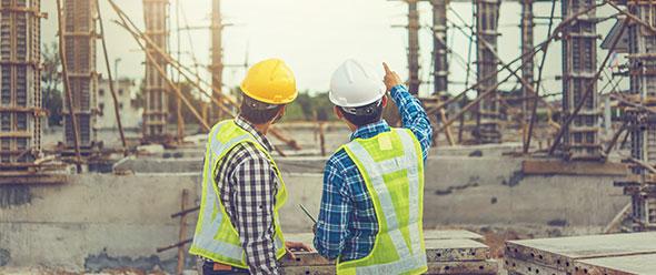 Dos personas supervisan una obra de construcción